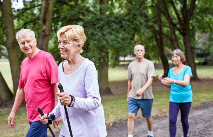 4 personnes seniors pratiquant la marche active dans un parc