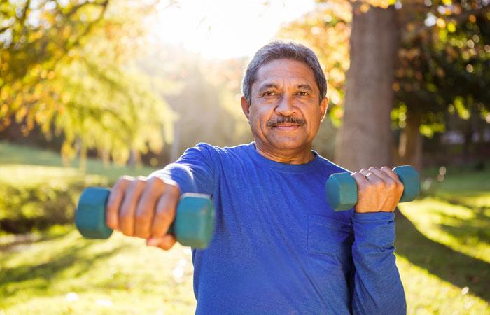 La photo présente un homme dans la cinquantaine d'origine ethnique faisant du sport dans un parc avec des mini poids dans les mains