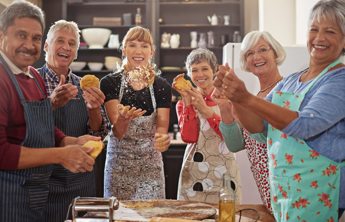 L'image présente différents adultes seniors et une jeune monitrice avec des tabliers de cuisine entrain de préparer des pâtes
